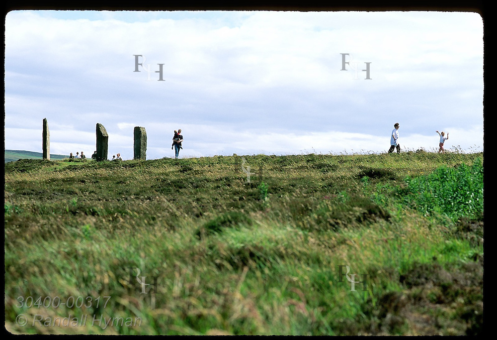 Family walks past stone megaliths of Ring of Brodgar (2800 BC) on a July day; Orkney Islands. Scotland