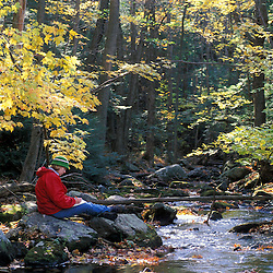 A young woman writes in her journal next to a small brook on a recently purchased TPL property.  Goshen, CT