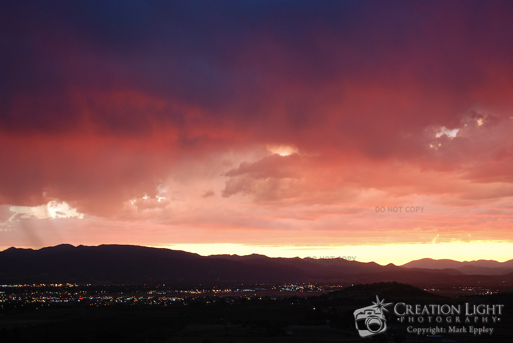 Colorful sunset in Medford, Oregon.  The setting sun casts a pink and purple hues on the clouds.   Medford is located in Southern Oregon in the Rogue Valley with mountains on the west and east sides of the valley.