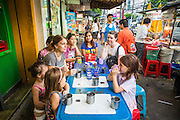 01 APRIL 2013 - BANGKOK, THAILAND:    The Hupes gather around a table at a Bangkok street food stand for dinner. Left to right: Arielle Hupe, 4, her friend, Lydia Thapa, 2.5 yrs old, Amy Hupe, Amita Thapa, 13, Amy's friend, Mina Thapa (Lydia and Amita's mother), Naamfon Boonlab (who works with the Hupes), Molly Evans (also works with the Hupes) and their older daughter Elijah Hupe, 6.    PHOTO BY JACK KURTZ