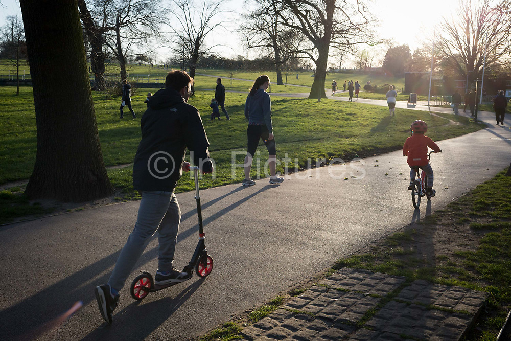 The day after UK Prime Minister Boris Johnson imposed unprecedented restrictions of movement for millions of Britons who were told to stay at home unless their key jobs or journeys were essential. Told to take a single exercise session per day, south Londoners use their local green space for sunset runs and cycling in Brockwell Park in Herne Hill SE24, on 24th March 2020.
