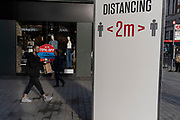 Londoners pass a social distancing sign that urges the public to keep 2 metres apart on Oxford Street during the second (Autumn) wave of the Coronavirus pandemic, on 8th October, 2020, in London, England.
