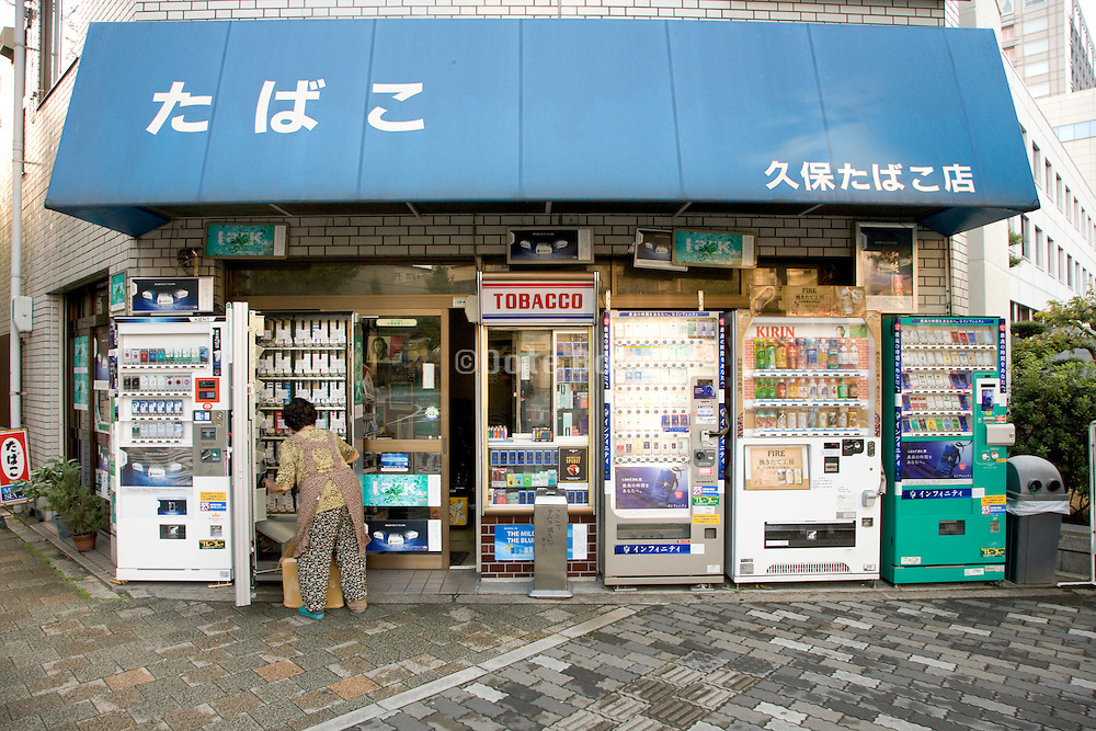 cigarettes and soda vending machines outside a small grocery store in Japan being restocked by an elderly woman