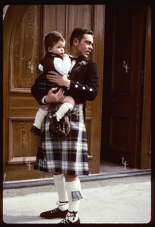 Groomsman in kilt holds ringbearer, also in kilt, in his arms outside church; Anstruther. Scotland