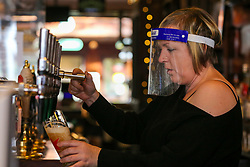 © Licensed to London News Pictures. 26/10/2020. London, UK. A barmaid wearing a face shield prepares a drink in a Wetherspoons pub in north London. The hospitality industry estimates that pubs, bars and restaurants have spent £900million on screens, masks and hand sanitisers to make their venues safe for reopening, following the easing of COVID-19 lockdown restrictions. It has been reported that each pub has spent more than £10,000 adapting the interiors of their venues but with the latest restrictions, many now only serve customers outside their premises. Wetherspoons has spent £13.1million on getting its 875 pubs ready. Photo credit: Dinendra Haria/LNP