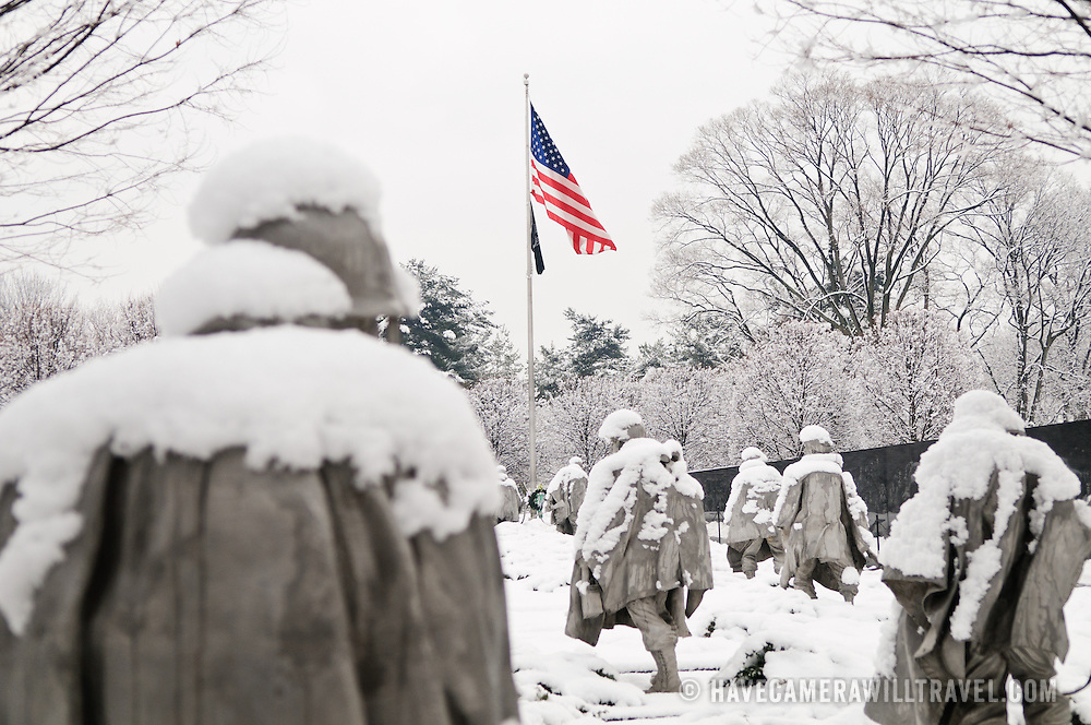 """The Korean War Veterans Memorial on the National Mall on a winter morning after heavy snow. The Korean War Veterans Memorial, unveiled in 1992, sits on the northwestern end of the National Mall, not far from the Lincoln Memorial. It consists of several elements designed by different people and groups. It has a triangular footprint with the main elements being """"The Column"""" consisting of 19 stainless steel solders, each over 7 feet tall, and a reflective granite wall etched with the faces of thousands of Americans who lost their lives in the war. At one end of the triangle, behind the soldiers, is a grove of trees. At the other is a large American flag and a small Pool of Remembrance. Among the designers were Frank Gaylord (the soldiers) and Louis Nelson (the reflecting granite wall)."""