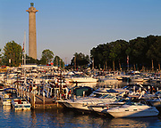 Boats docked at Put-in-Bay with Perry's Victory International Peace Memorial, rising 352 feet beyond, South Bass Island, Lake Erie, Ohio.