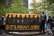 """Workers from the Painters and Allied Trades International Union hold a large banner reading """"It's about jobs! Let's get American working again."""""""