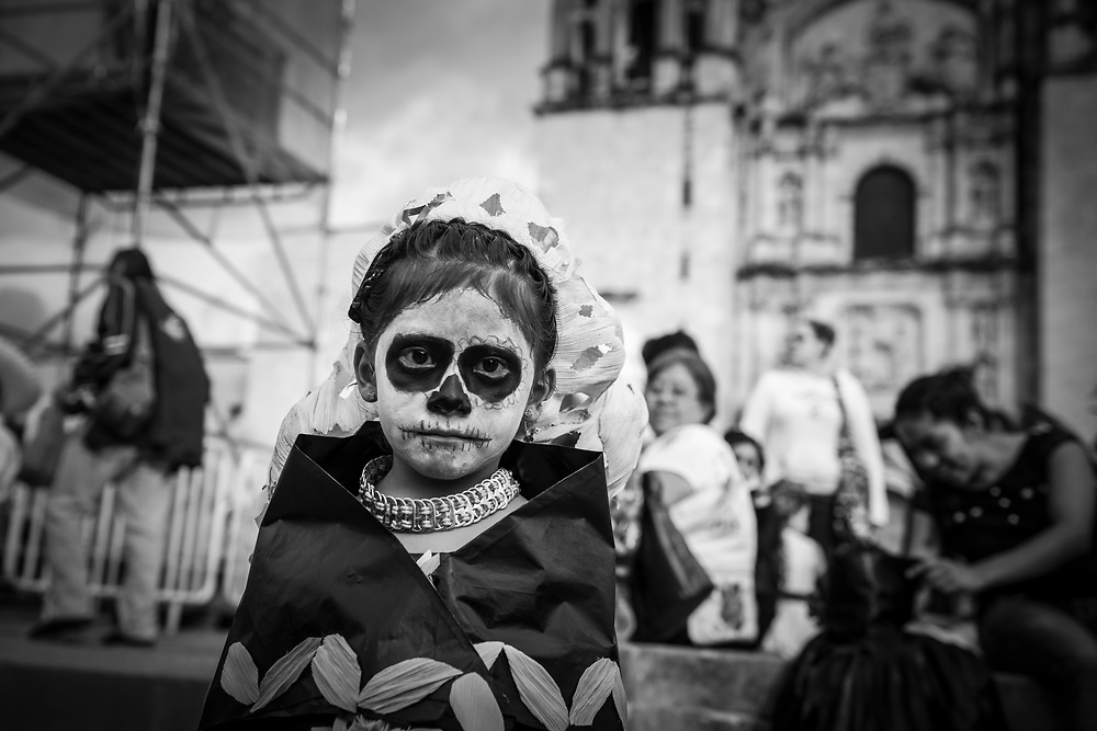 """A Mexican girl stands outside the Church of Santo Domingo de Guzmán in Oaxaca, Mexico. She and other children are dressed for Day of the Dead celebrations (""""Día de los Muertos"""" in Spanish)."""