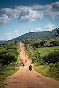 Motorbike drives along dirt road track past walking pedestrians on their way to Mbulu, Manyara district, Tanzania, East Africa.  (photo by Andrew Aitchison / In pictures via Getty Images)
