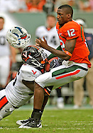 Virginia linebacker Cam Johnson (56) face masks and rips the helmet off Miami's quarterback Jacory Harris (12) in the third quarter as the University of Miami host the Virginia Cavaliers at Land Shark Stadium on Saturday November 7.