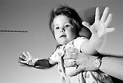 """""""Flight to Portugal."""" An eleven month-old child stands on a restaurant  table and is held by her mother whilst holidaying on the Algarve, southern Portugal. Caught with side-lit flash and ambient Mediterranean evening light, her with arms and fingers are outstretched and the balancing infant girl who is learning to stand on her own before attempting to walk, pretends to fly in mid-air, relishing a sense of space and freedom. We see the experience of an adult encouraging a developing human being with the confidence to stand erect with back straight. This is from a documentary series of pictures about the first year of the photographer's first child Ella. Accompanied by personal reflections and references from various nursery rhymes, this work describes his wife Lynda's journey from expectant to actual motherhood and for Ella - from new-born to one year-old."""