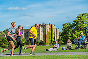 The run (the final event) passes the castle and supporters enjoying the sun - Competitors enjoy the warm sunny conditions while participating in the Hever castle Triathlon.