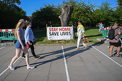 © Licensed to London News Pictures. 25/04/2020. London, UK. A sign directs members of the public to stay at home on the the river in Hammersmith. People make the most of the fine weather along the river on a weekend where the public are urged to observe social distancing and only go outside where absolutely necessary.  Photo credit: Guilhem Baker/LNP