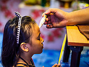 """29 MARCH 2017 - BANG KRUAI, NONTHABURI, THAILAND:  A girl is annointed after going through a """"Resurrection Ceremony"""" at Wat Ta Kien (also spelled Wat Tahkian), a Buddhist temple in the suburbs of Bangkok. People go to the temple to participate in a """"Resurrection Ceremony."""" Groups of people meet and pray with the temple's Buddhist monks. Then they lie in coffins, the monks pull a pink sheet over them, symbolizing their ritualistic death. The sheet is then pulled back, and people sit up in the coffin, symbolizing their ritualist rebirth. The ceremony is supposed to expunge bad karma and bad luck from a person's life and also get people used to the idea of the inevitability of death. Most times, one person lays in one coffin, but there is family sized coffin that can accommodate up to six people. The temple has been doing the resurrection ceremonies for about nine years.         PHOTO BY JACK KURTZ"""