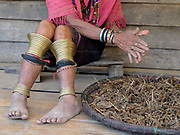 An elderly Kayaw ethnic minority woman wearing traditional clothing and brass leg rings prepares millet for making the local traditional alcohol in Ya A Pra village, Kayah State, Myanmar on 21st November 2016