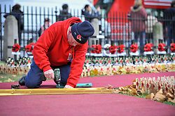 © Licensed to London News Pictures. 08/11/2017. London, UK.  Volunteers help to lay a red carpet through the Field of Remembrance outside Westminster Abbey as preparations for Armistice Day and Remembrance Sunday begin in, and around, Westminster.  Photo credit: Stephen Chung/LNP