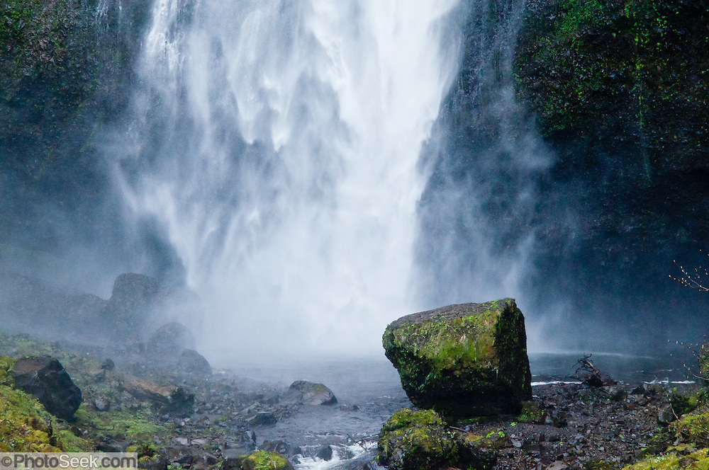 Multnomah Falls upper tier (542 feet plunge) blasts mist onto a mossy boulder in Columbia River Gorge National Scenic Area, located on Historic Columbia River Highway and Interstate 84, Oregon, USA.