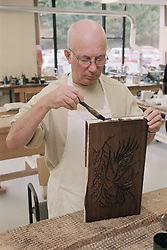 Man varnishing piece of carved wood during occupational therapy session at clinic,