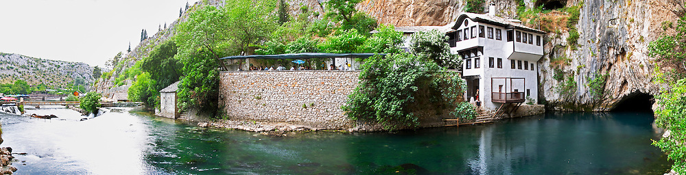 The source of the Buna river at the old Muslim monastery called the House of the Whirling Dervishes, below an impressive vertical cliff drop. Wide panorama. The source of the Buna river and the house of the Whirling Dervishes, an old Muslim monastery, Blagaj. Federation Bosne i Hercegovine. Bosnia Herzegovina, Europe.