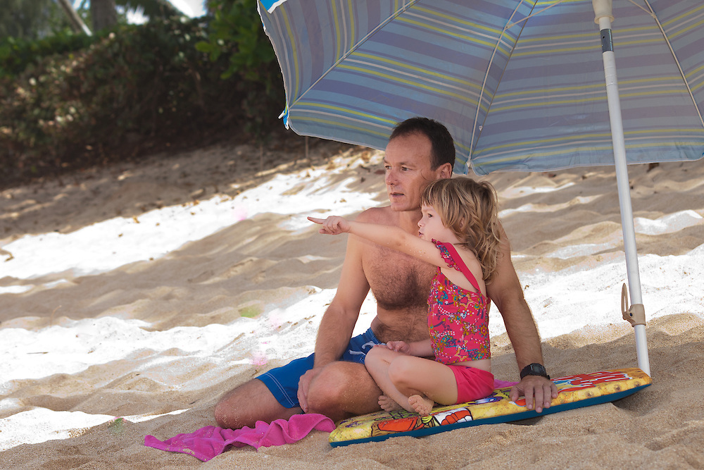 A little girl points at the surfers with her father on the beach in Hawaii