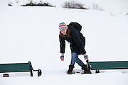 Young woman avoiding deep snow to reach park bench in snowy Tromso, Norway