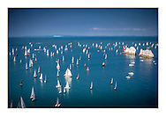 One of those amazing 'time stands still' moments, although stillness is not what the sailors like! A gaff cutter sits mid-fleet at The Needles during the 2014 Round the Island Race. Isle of Wight, England. <br /> Photograph by Christopher Ison ©<br /> 07544044177<br /> chris@christopherison.com<br /> www.christopherison.com