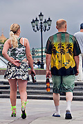 Moscow, Russia, 16/07/2006..Russian couple in beachwear strolling through Manezh Square next to the Kremlin and Red Square.