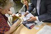 Nederland, Nijmegen, 19-3-2014Bij het stembureau in het informatiecentrum van de gemeente wordt om 21.00 uur de stembus geleegd en de stemmen, stembiljetten, geteld met extra vrijwilligers. Ook worden de stempassen van de mensen die gestemd hebben in een enveloppe gedaan en verzegeld. Per partij wordt een stapel gemaakt. Het tellen van de stemmen is openbaar, maar er komt maar zelden iemand naar kijken.Foto: Flip Franssen/Hollandse Hoogte