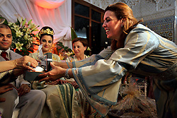 Sanaa Bencheqroun, 45, helps Meryem Benanine, 32, and Nabil Abou et Ainine, 33, during the ring exchange part of their ceremony in Casablanca, Morocco on May 10, 2009. Bencheqroun works as a neggafa, a kind of full service Moroccan wedding planner, where everything is provided from traditional wedding attire to band selection and assistance on the actual wedding day. The couple married in a traditional ceremony arranged by their families.