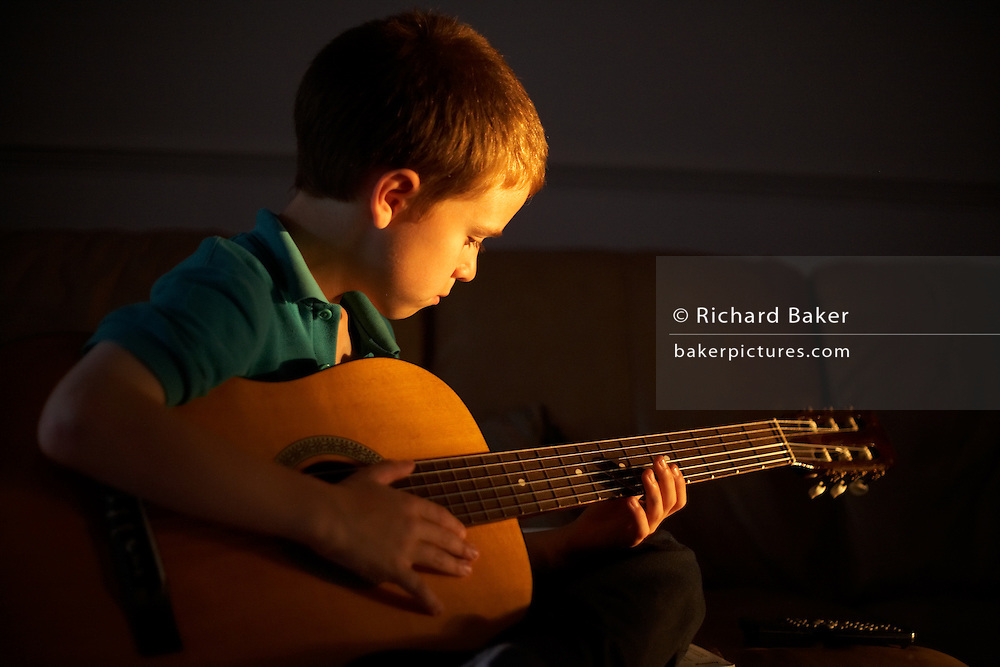 A 9 year-old boy musician plays an acoustic guitar at home lit by late summer sinlight, London England.