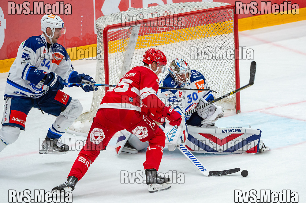 LAUSANNE, SWITZERLAND - OCTOBER 01: Cory Emmerton #25 of Lausanne HC battles for the puck with Goalie Lukas Flueler #30 of ZSC Lions during the Swiss National League game between Lausanne HC and ZSC Lions at Vaudoise Arena on October 1, 2021 in Lausanne, Switzerland. (Photo by Robert Hradil/RvS.Media)