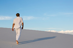man walking up a sand dune at sunset