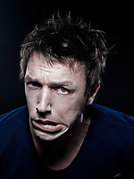 studio portrait on black background of a funny expressive caucasian man grimacing annoyed