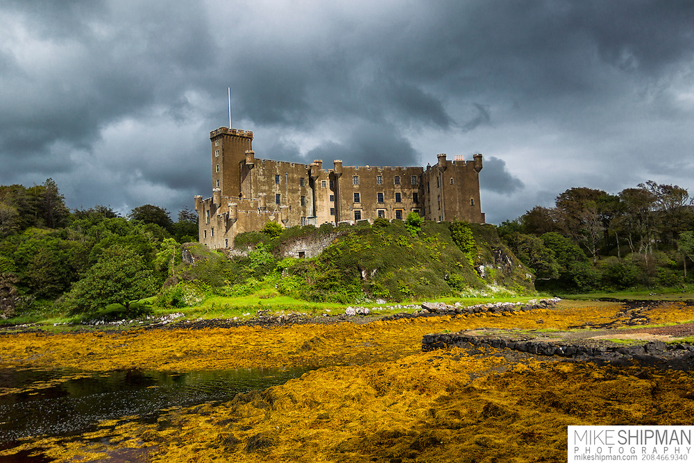 Dunvegan Castle in sunlight during clearing storm, home of the Clan McCleod for over 800 years. Isle of Skye, Scotland, UK