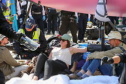 © Licensed to London News Pictures. 19/04/2019. London, UK. Police officers un-bonds the environmental activist  on the fifth day of the climate change protest by the Extinction Rebellion movement group who have glued themselves. Photo credit: Dinendra Haria/LNP
