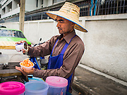 18 FEBRUARY 2015 - BANGKOK, THAILAND: A street food vendor prepares a crushed ice dessert for high school student after school in the Kudeejeen neighborhood in Bangkok. Santa Cruz church was established in 1770 and is the heart of the community. It is one of the oldest and most historic Catholic churches in Thailand. The church was originally built by Portuguese soldiers allied with King Taksin the Great. Taksin authorized the church as a thanks to the Portuguese who assisted the Siamese during the war with Burma. Most of the Catholics in the neighborhood trace their family roots to the original Portuguese soldiers who married Siamese (Thai) women. There are about 300,000 Catholics in Thailand in about 430 Catholic parishes and about 660 Catholic priests in Thailand. Thais are tolerant of other religions and although Thailand is officially Buddhist, Catholics are allowed to freely practice and people who convert to Catholicism are not discriminated against.        PHOTO BY JACK KURTZ