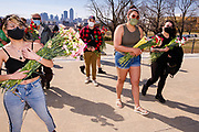 09 MARCH 2021 - DES MOINES, IOWA: People carry flowers to a flower filled coffin during a memorial service for the 5,574 Iowans killed by COVID-19 in the one year since the pandemic started. Each flower represented an Iowan killed in the pandemic. About 75 people attended the service. The first three cases of the Coronavirus (SARS-CoV-2), all Iowans who had traveled to Egypt on a cruise, were reported to the Iowa Department of Public Health on March 8, 2020. The first fatality in Iowa was reported on March 25, 2020.    PHOTO BY JACK KURTZ