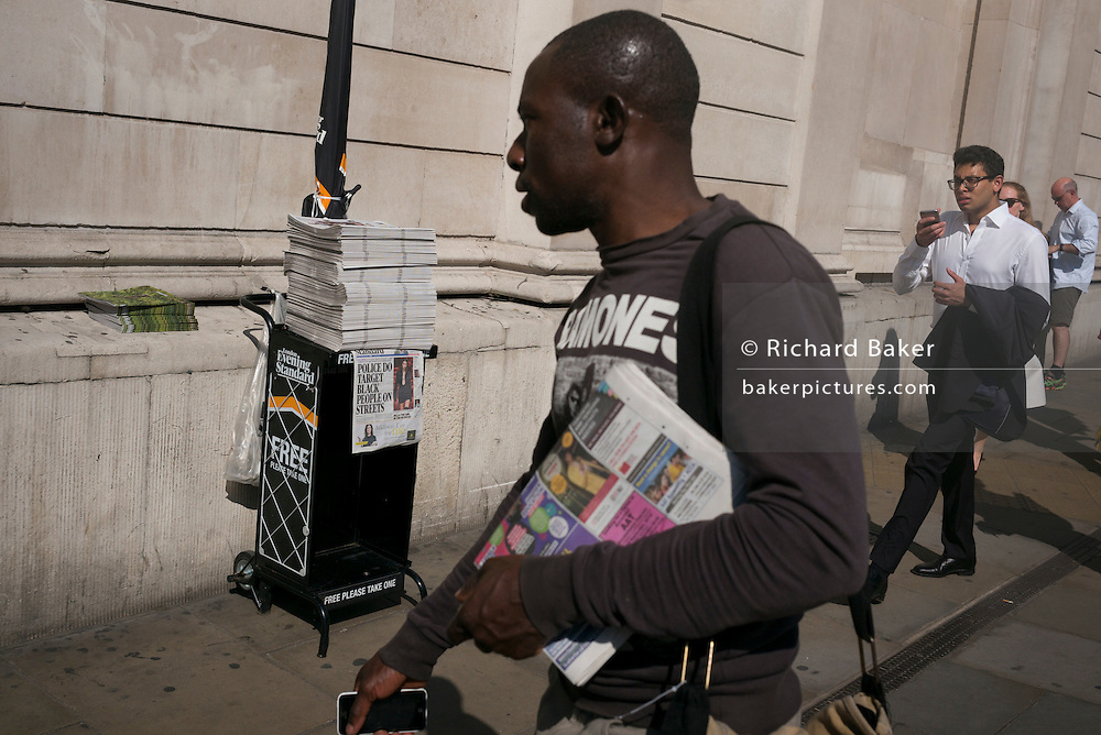 A man walks past an Evening Standard headline about police stopping black people on 13th September 2016, in the City of London, England.