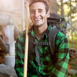 A young man wth his canoe paddle next to Long Pond in Maine's north woods. At the Appalachian Mountain Club's Gorman Chairback Lodge. Near Greenville, Maine.