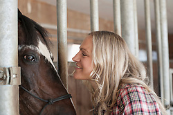 Mid adult woman face to face with horse in barn and smiling, Bavaria, Germany
