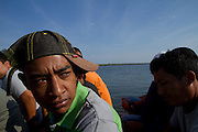 Migrants travel in a boat in San Pedro River, north of Guatemala. (Photo: Prometeo Lucero)