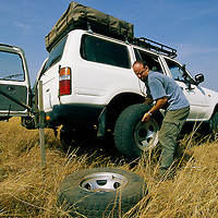 Africa, Kenya, Masai Mara Game Reserve, (MR) Photographer Paul Souders changes tire of Toyota Land Cruiser on safari