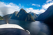 Flying over Milford Sound in Fiordland National Park, Southland region, South Island of New Zealand. We enjoyed an easy 3-day version of the Hollyford Track: Day 1: fly from Milford Sound to Martins Bay, walk to its oceanfront Hut, and see New Zealand fur seals. Day 2: jetboat on Lake McKerrow to Pyke River Confluence, hike to Hidden Falls Hut for overnight lodging. Day 3: tramp out to Hollyford Road end to our prearranged car shuttle. In 1990, UNESCO honored Te Wahipounamu - South West New Zealand as a World Heritage Area.