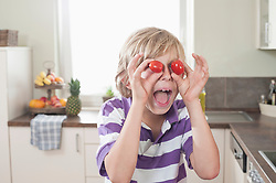 Playful boy making face with tomatoes, Bavaria, Germany