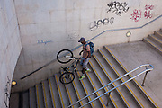 A youth manoeuvres his bike down steps at Alameda metro station, Lisbon, Portugal.