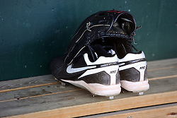 18 May 2012:  Baseball shoes (cleats) and a baseball glove sitting on a shelf above the back of the bench during a Frontier League Baseball game between the Windy City Thunderbolts and the Normal CornBelters at Corn Crib Stadium on the campus of Heartland Community College in Normal Illinois This image available for EDITORIAL USE ONLY. A release may be required. Additional information by contacting alook at alanlook.com