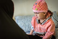 24 February 2020, Jerusalem: Four-year-old Lana, from Gaza, is tended to by her mother Hiba at the Augusta Victoria Hospital in Jerusalem. With the support of the Lutheran World Federation, Lana has come to the hospital to spend a full month there, in order to go through radiotherapy treatment for a brain tumor.
