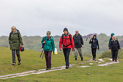 Licensed to London News Pictures. 13/05/2021. London, UK. Hikers brave the weather Richmond Park in south west London this morning as miserable May continues with grey skies and prolonged rain with temperatures down to 12c today. Weather forecasters predict sunshine and showers for most of the weekend and next week with chilly nights in the South East as the wet weather continues. Photo credit: Alex Lentati/LNP