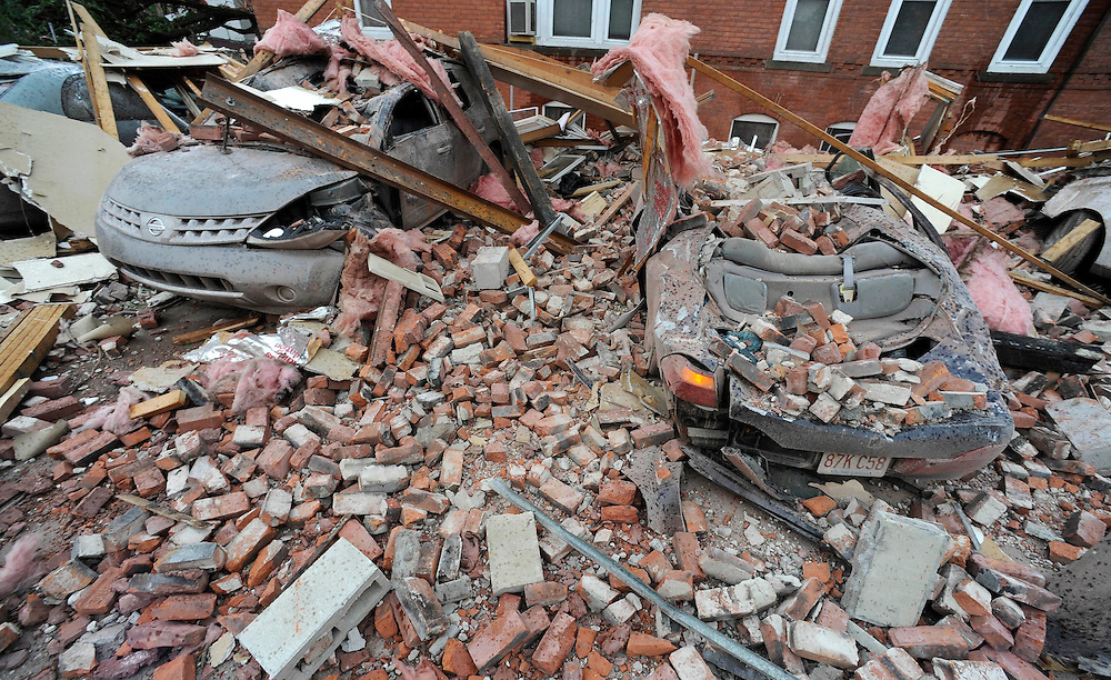 Bricks and debris that fell from a building lay on top of cars after a report of a tornado in Springfield, Mass., Wednesday, June 1, 2011. An apparent tornado struck downtown Springfield, one of Massachusetts' largest cities, scattering debris, toppling trees, and frightening workers and residents. (AP Photo/Jessica Hill)
